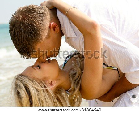 Playful couple making love on the beach