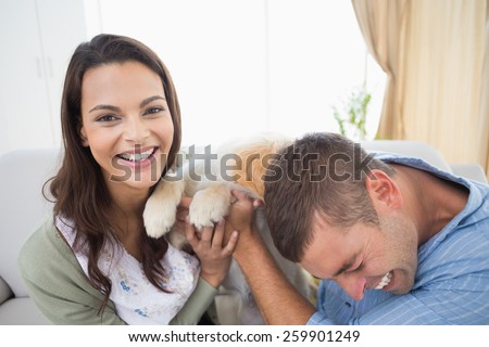 Playful couple with puppy at home