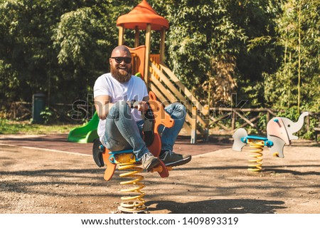 Playful crazy man (dad) riding wooden rocking horse in a park - adult guy (hipster with beard) having fun on a playground Stock photo ©