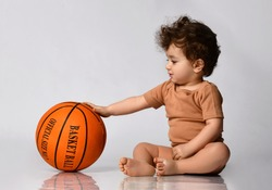Playful curly little boy, dressed in a bodysuit, sits barefoot and plays new basketball on a gray background. Place for text. The concept of an active childhood.