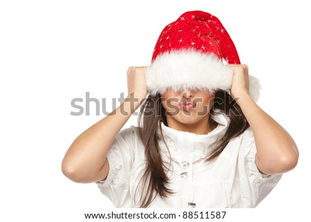 Playful cute young woman in Santa hat having fun pulling down the hat over the eyes on white background.
