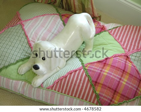 Playful elegant porcelain dog on checkered pillow