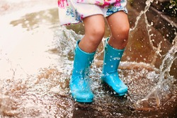 Playful excited preschool child in casual clothes and rubber boots with blue umbrella laughing and jumping in puddle smiling at camera while playing in park