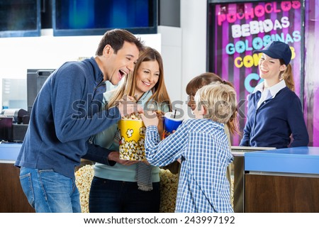 Playful family of four enjoying snacks while female worker standing at cinema concession stand