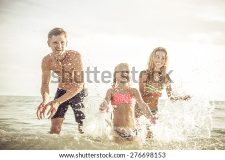 playful family spraying water and having fun. concept about vacation, summer,fun, family and people.