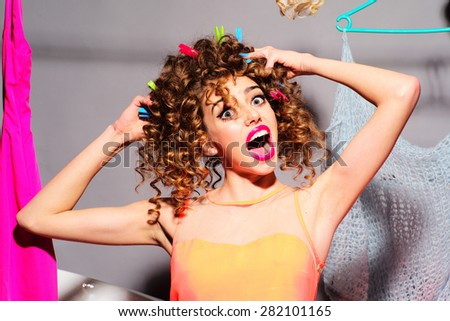 Playful fiefy beautiful girl with curly hair and bright make up touching her hair looking forward with surprised eyes and open mouth standing on grey wall background, horizontal picture