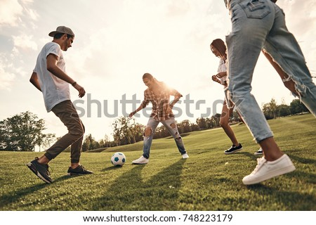 Playful friends. Group of young smiling people in casual wear playing soccer while standing outdoors - Shutterstock ID 748223179