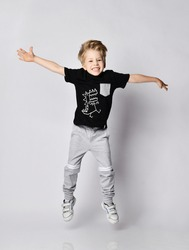 Playful frolic blond kid boy in sunglasses, black t-shirt with dinosaur print and gray pants jumps with hands spread wide, has fun over gray background