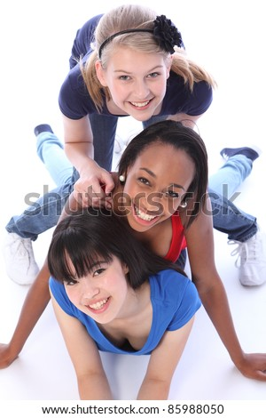 Playful fun by three multi cultural teenage school student friends made up of mixed race african american, oriental Japanese and caucasian all with big smiles having a laugh.