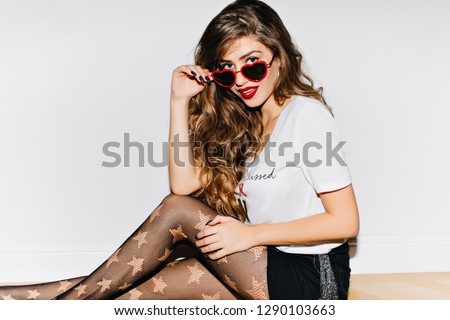 Stock Photo Playful girl in red sunglasses sitting on white background. Surprised young woman with dark wavy hair chilling during photoshoot.