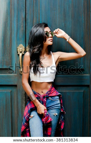 Playful girl,pretty face,fashion sunglasses woman.Cute Chinese Asian/Caucasian woman casual urban spring-summer outfit,denim fashionable outfit,street city style,amazing hairstyle,wavy volume hair