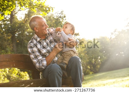 Playful grandfather spending time with his grandson in park