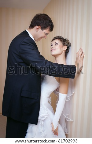 Playful groom with smiling bride standing indoors