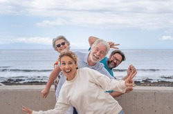 Playful group of multigeneration family looking at camera joking outdoor by the sea. Horizon over water and cloudy sky