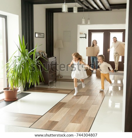 Playful happy kids running into new big own beautiful house, family moving in day concept, excited children exploring home interior having fun together, parents holding cardboard boxes at background