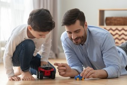 Playful happy young single father and cute little son racing holding toy cars on warm heated floor at home, small preschool child boy having fun bonding with dad playing funny game activity together