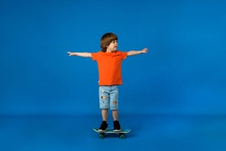 playful little boy with brown hair rides a skateboard on a blue background with a place for text