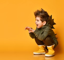 Playful little brunet boy in brown dino hoodie sits squatting, growling, scaring, holding hands like beast claws against orange studio background. Childhood, fashion, advertising.