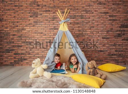 Playful little children in handmade tent indoors Stock photo ©