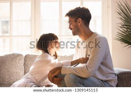 Playful little daughter playing funny game as doctor having fun with dad sitting on couch, cute child girl pretending nurse in medical uniform holding stethoscope listening to father patient at home