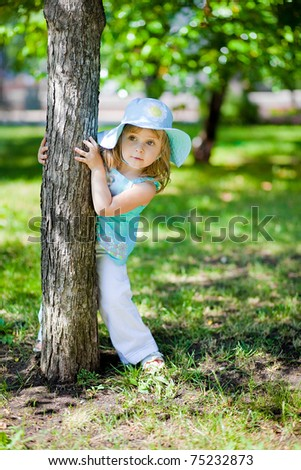 playful little girl  in a summer park
