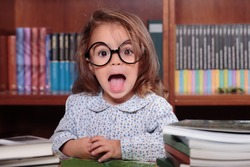Playful little girl in glasses sitting at teacher's table against of shelves with books
