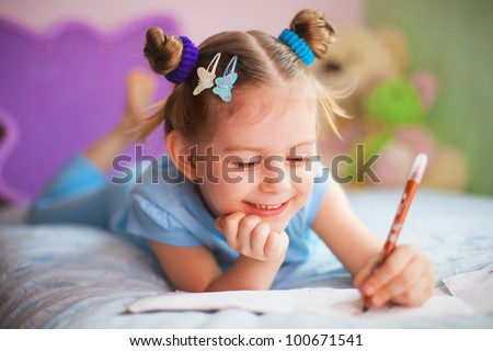 Playful little girl painting in her room
