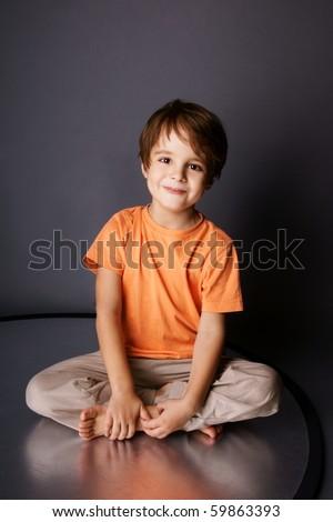 Playful little smiling boy sitting in a lotus pose, studio shot