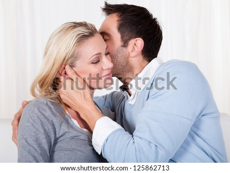 Playful lovely couple sitting together at home