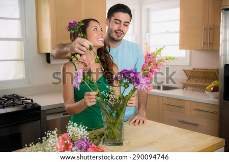 Playful man and woman dating put flowers into a vase at home in the kitchen