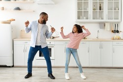 Playful Mood. Excited African American father and joyful girl dancing while cooking together at kitchen, fooling around, cheerful man holding whisk, spending free time with cute daughter