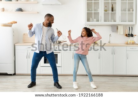 Playful Mood. Excited African American father and joyful girl dancing while cooking together at kitchen, fooling around, cheerful man holding whisk, spending free time with cute daughter Foto stock ©