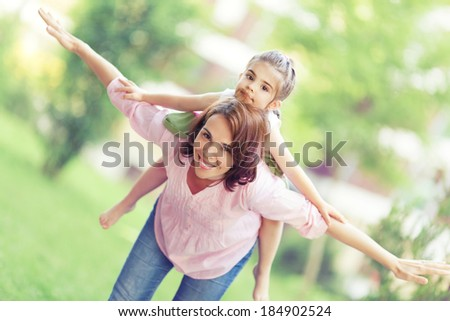 Playful mother and little daughter enjoying in nature.