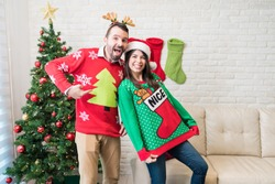 Playful partners showing their ugly sweaters while enjoying Christmas holiday at home