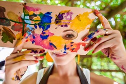 Playful portrait of a young gorgeous female artist painter covered in paint, looking and smiling at camera through her painter's palette. Creativity and individuality concept.