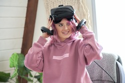 Playful pretty teen hipster girl with pink hair wear vr headset goggles on head holding digital controllers experiencing virtual reality immersive entertainment 3d 360 innovation technology at home.