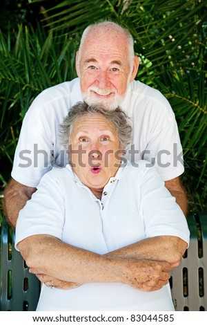 Playful senior man tickling his wife just as their portrait is taken.