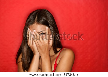 Playful shy woman hiding face laughing timid. Cute Chinese Asian / Caucasian woman smiling happy through hands. Red background.