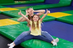 Playful silly mom with her teen daughter sitting at trampoline area of entertainment centre, showing thumbs up gesture. Mother and her child recommending to visit indoor kids playground