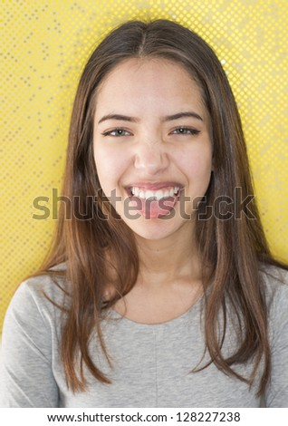 Playful teenage girl having fun and making a grimace in front of funky yellow dotted background