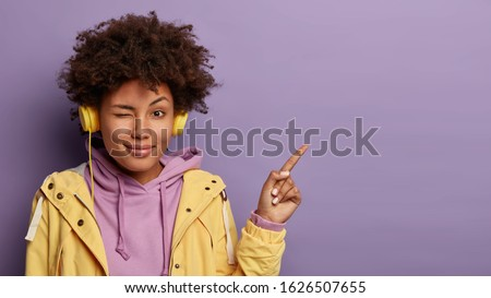 Playful woman blinks eyes, has appealing look, curly hairstyle, points index finger on copy space attracts your attention to advert listens music in playlist with modern headphones wears casual outfit