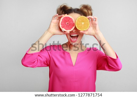 Playful woman holding halves of citrus fruits, covering eyes over grey background #1277871754