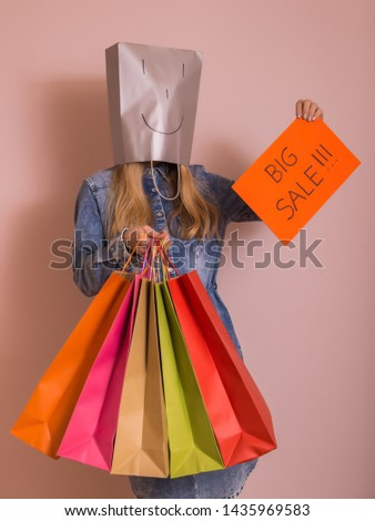 Playful woman holding shopping bags with bag on her head and paper with text big sale while standing in front of the wall. #1435969583