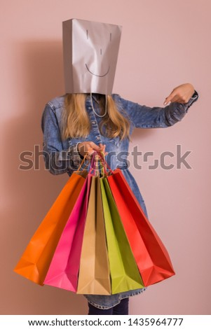 Playful woman holding shopping bags with bag on her head while standing in front of the wall. #1435964777