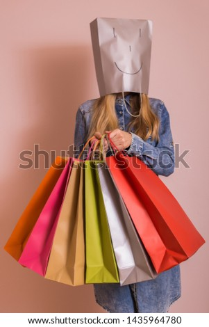 Playful woman holding shopping bags with bag on her head while standing in front of the wall. #1435964780