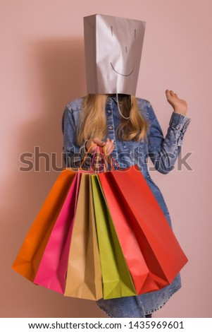 Playful woman holding shopping bags with bag on her head while standing in front of the wall. #1435969601