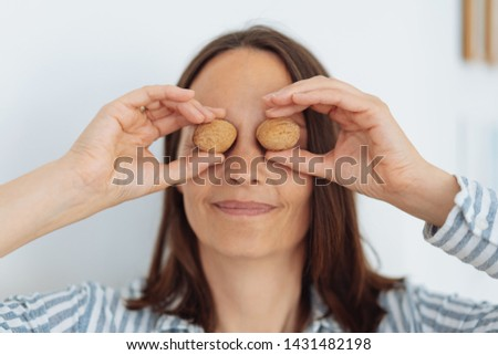 Playful woman holding whole fresh walnuts in their shells to her eyes with a happy smile #1431482198