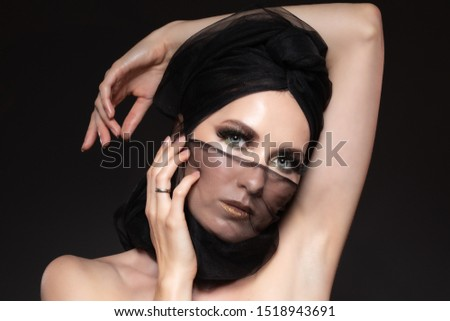 Playful woman in a turban looking at the camera. Slim European girl posing with a head scarf on a black background. #1518943691