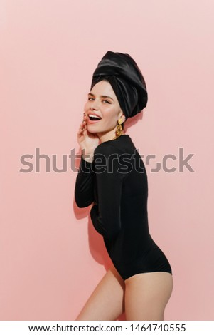 Playful woman in turban looking to camera. Slim european girl posing with head scarf on pink background. #1464740555