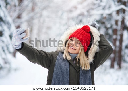 Playful woman making a selfie in winter forest  #1543625171